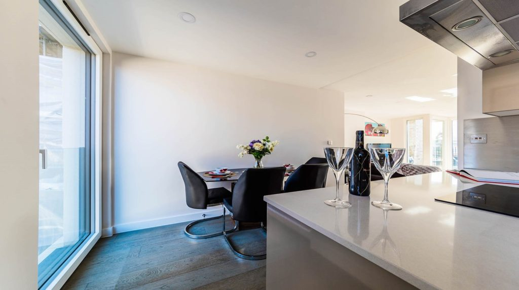A bottle of wine and a few glasses give your listing an air of comfort, alongside a cookbook and well-set dinner table your kitchen will pop out to guests and help secure those bookings.
