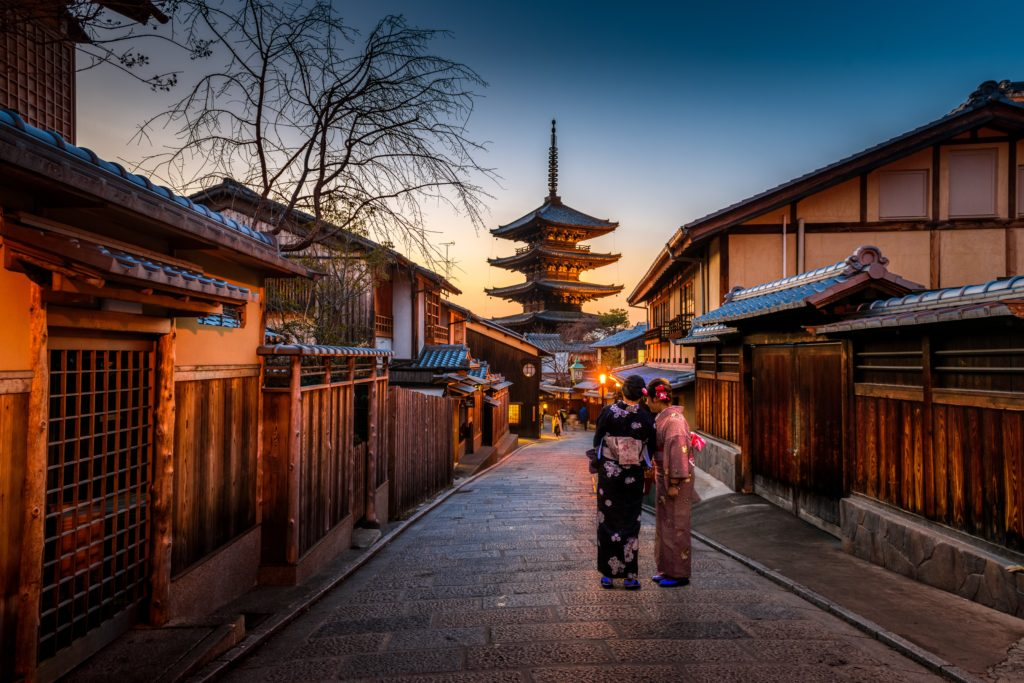 Kyoto Japan, two women in kimonos standing in front of a row of streets leading to a temple.