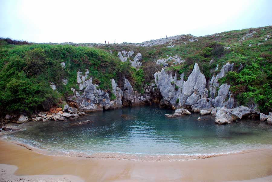 A sinkhole turned into a beach, surrounded by rocks and sand.