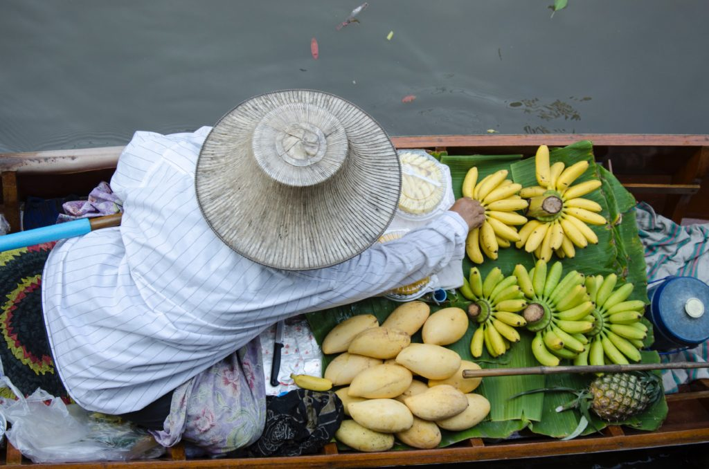 Person with hat on floating market boat