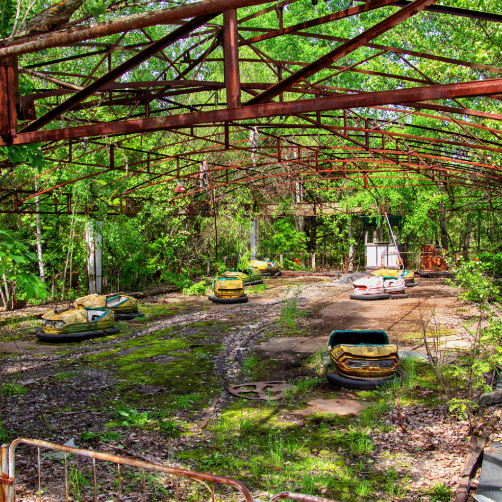 Bumper cars left abandoned in Chernobyl, the nuclear disaster zone, greenery is surrounding the structure and growing around the cars.